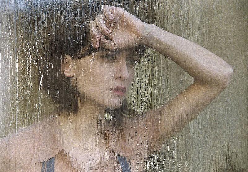 Девушка у окна, за которым идёт дождь.
